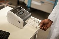 En lege skriver ut en medisinsk etikett på en Brother TD4550DNWB skrivebords etikettskriver