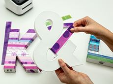 A woman is wrapping a full colour label printed on the Brother Design and Craft label printer, around a large ampersand character as part of her custom home decoration