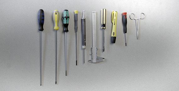 Ruuvimeisselit, mittaharpit ja sakset pöydällä