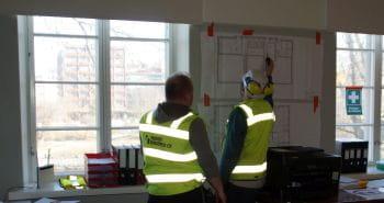 To personer i gule refleksvester og hjelm ser på plantegninger som henger på veggen inne på et kontor