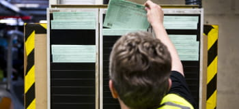 En arbeider plasserer et dokument i en dokumenttavle