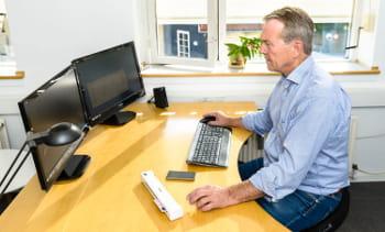 En ansatt fra Enevold sitter ved skrivebordet å jobber på datamaskinen