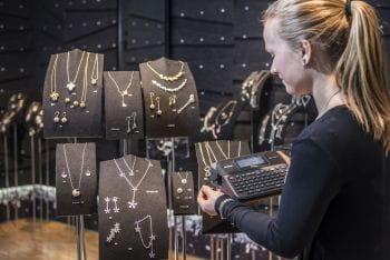 En ansatt hos Kalevala Koru skriver ut merkelapper på en P-touch merkemaskin som festes på smykkestativ i butikken