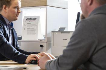 To menn sitter ved et bord i en samtale på et kontor med Brother skrivere i bakgrunnen