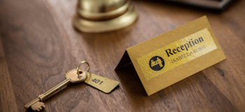 En nøkkel og et skilt i en resepsjon med Brother P-touch merkelapp i sort på gull