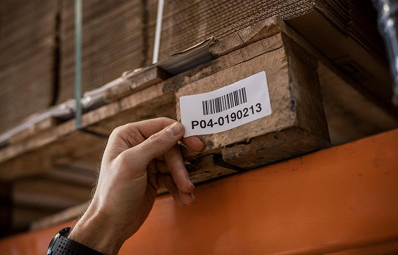 En strekkodeetikett plasseres på en pall på et lager