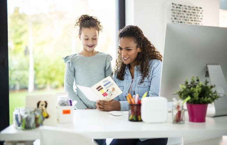 En jente viser en kvinne et kort hun har laget som er merket med merkelapper fra en Brother P-touch CUBE merkemaskin