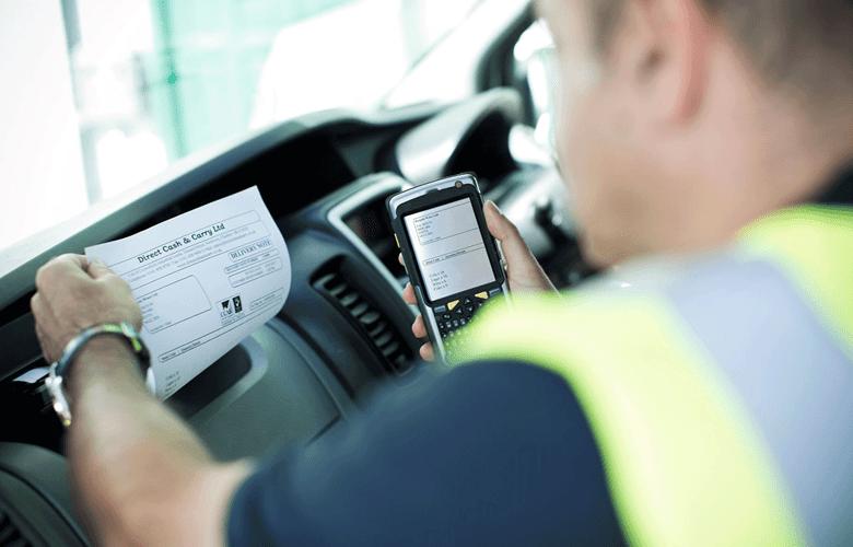 En mann med gul vest skriver ut på en mobil dokumentskriver i PJ-serien som er montert i bilen