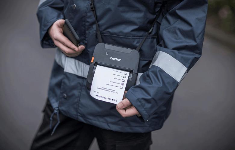 En parkeringsvakt skriver ut en kvittering på en Brother mobil skriver i RJ serien