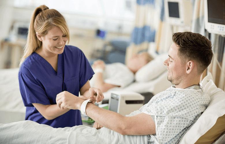 En helsearbeider fester et ID-armbånd rundt håndleddet på en pasient