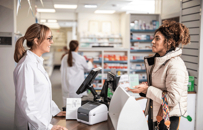 En apotekansatt ved en disk med en Brother TD etikettskriver i samtale med en kunde