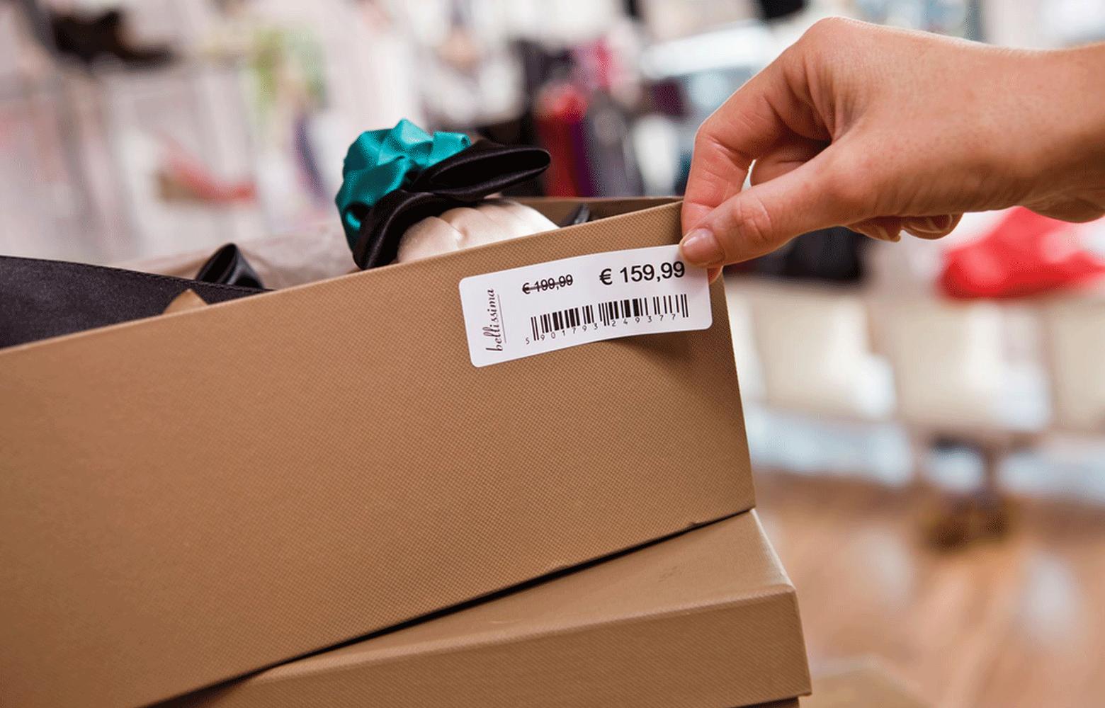 En butikkansatt fester en etikett med strekkode og pris på en skoeske
