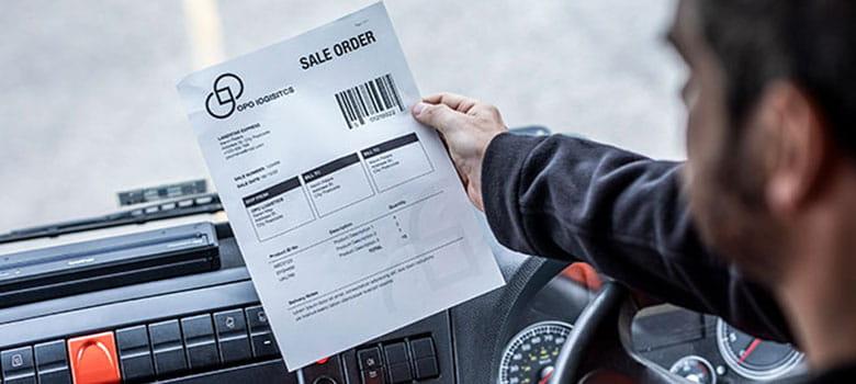 En mann holder et leveransedokument i hånden som er skrevet ut på en Brother PJ mobil skriver som er fastmontert i bilen