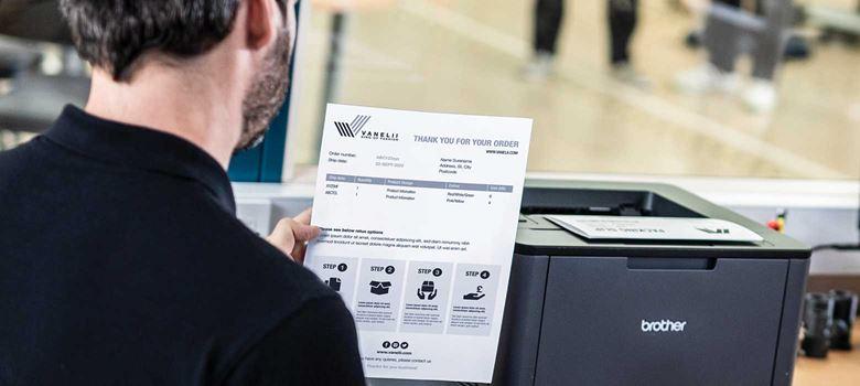 En lagerarbetare står vid en Brother-laserskrivare och håller ett dokument