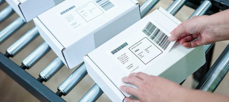 Valkoiseen pakkaukseen kiinnitetään toimitustiedot sisältävää tarraa
