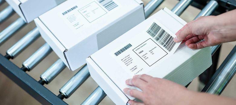 En person fäster en leveransetikett på en vit låda som ligger på ett transportband