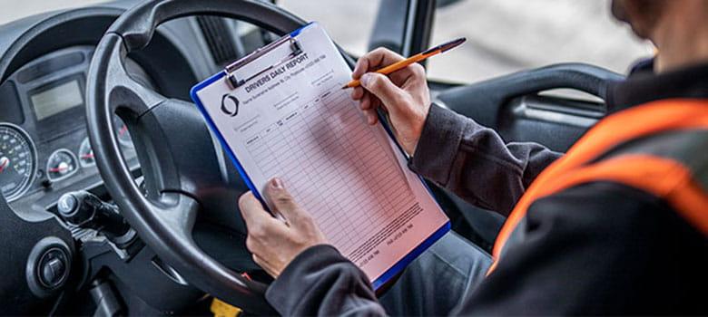 En sjåfør sitter i et kjøretøy og fuller ut et dokument