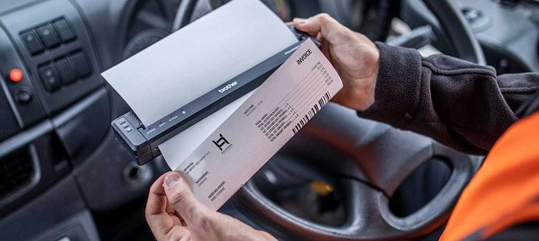 En sjåfør sitter i kjøretøyet og skriver ut et dokument på en Brother mobil skriver i PJ-serien