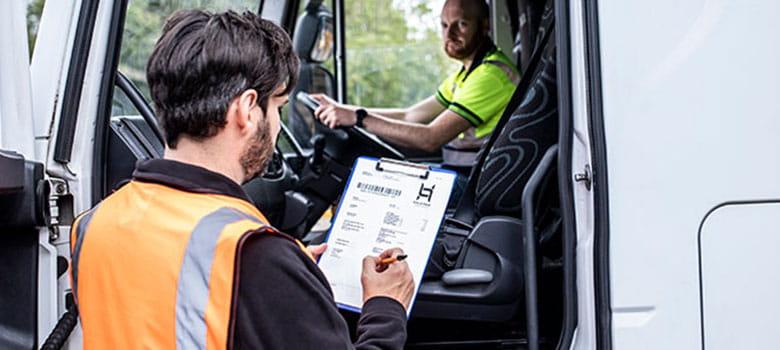 En mann i orange vest fyller ut et dokument mens han er i samtale med en sjåfør som sitter i lastebilen