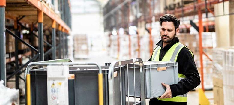En lagerarbeider plasserer en grå plastkasse i et stålbur