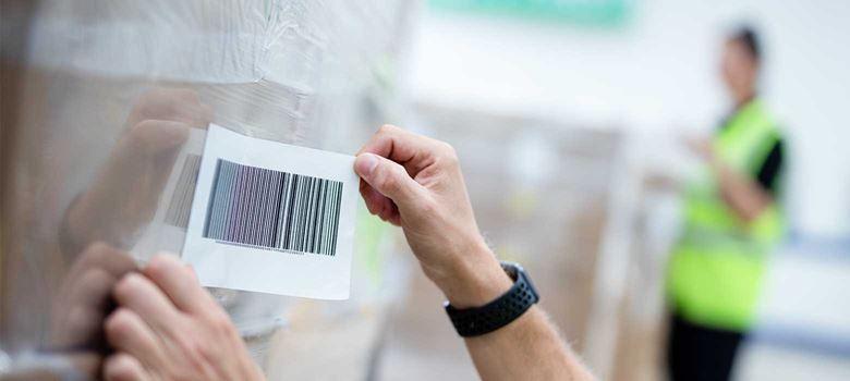 Etikett med strekkode festes på en pall med esker som har plast rundt seg på et lager