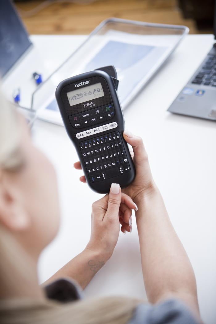 En kvinne skriver ut etiketter på en Brother håndholdt P-touch merkemaskin