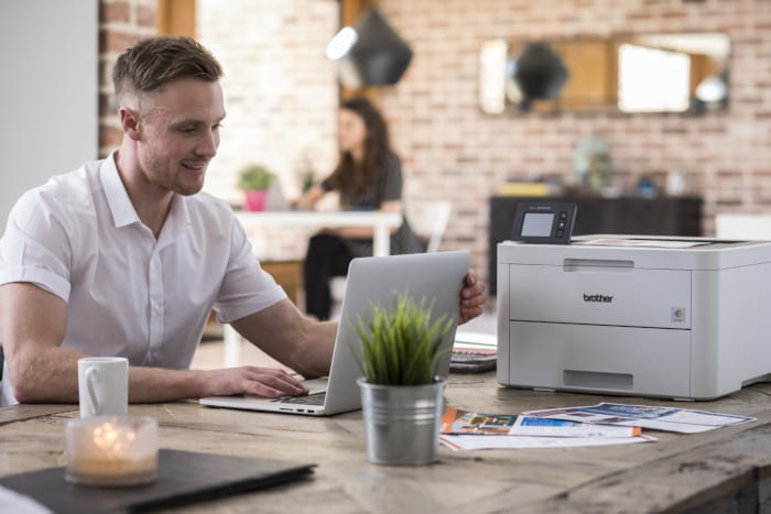 Man sitting at desk with printer nearby