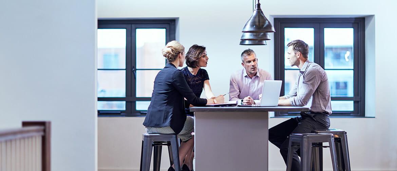 En gruppe mennesker i samtale rundt et bord