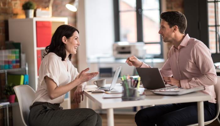 En kvinne og en mann sitter i en samtale ved et skrivebord
