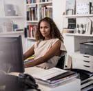 En kvinne sitter ved skrivebordet og jobber på en datamaskin