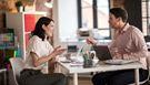En mann og en kvinne sitter i en samtale ved et skrivebord på et kontor