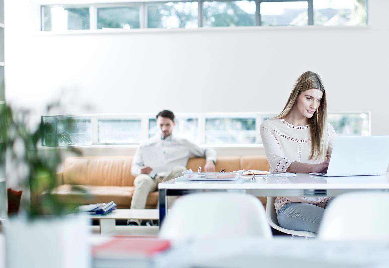 En mann sitter i en sofa en kvinne sitter ved et skrivebord med en laptop