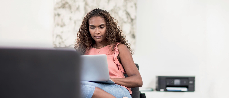 Mulher com cabelo rizadd sentado com laptop