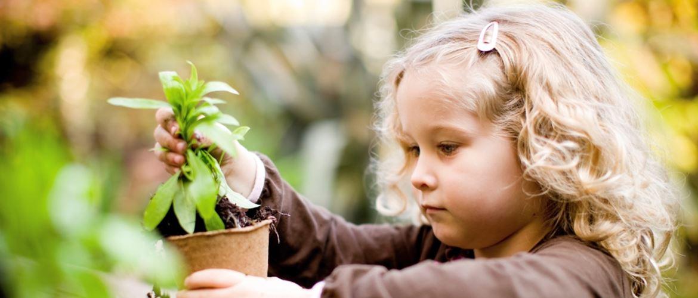 Niña de pelo rubio cogiendo una maceta y una planta