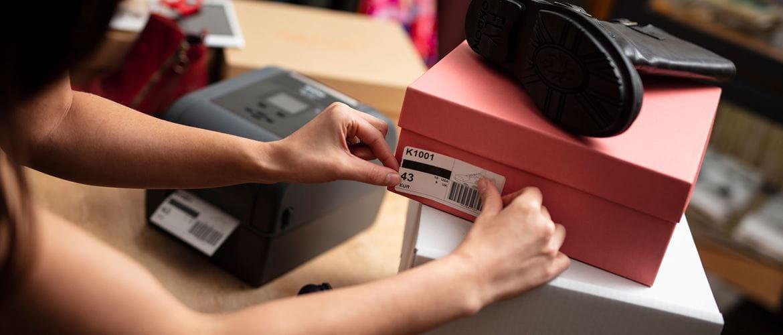 Lady sticking shoebox label onto a pink shoe box in front of Brother TD desktop label printer