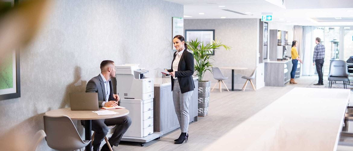 Man sat at table, woman in suit stood at printer in office, chairs, tables, plants, people in the background