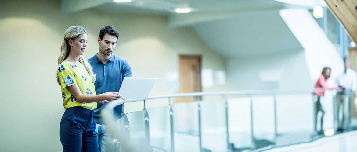 Man and woman stood in corridor looking at laptop