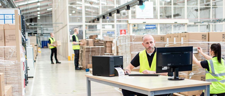 Man in high visibility vest sat at desk printing on TJ industrial label printer in warehouse