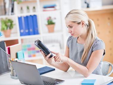Mulher com rotuladora Brother e laptop