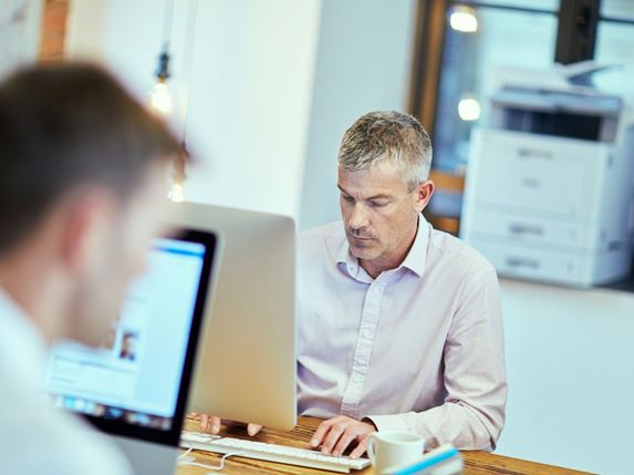 Dois homens trabalhando com laptops