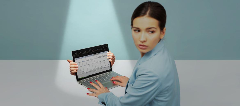 Девушка с ноутбуком оглядывается через плечо