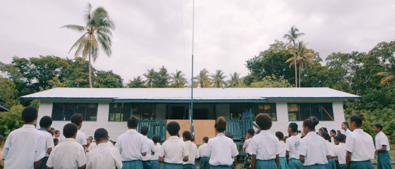 Children wearing uniforms in front of the school