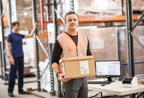 Man with short brown hair in orange hi-vis holding brown box in warehouse, table, monitor, keyboard, mouse, racking