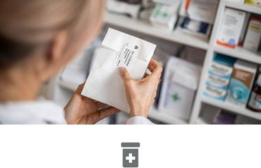 Female pharmacist labelling medication in pharmacy