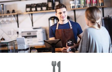 Man in coffee shop serving female customer
