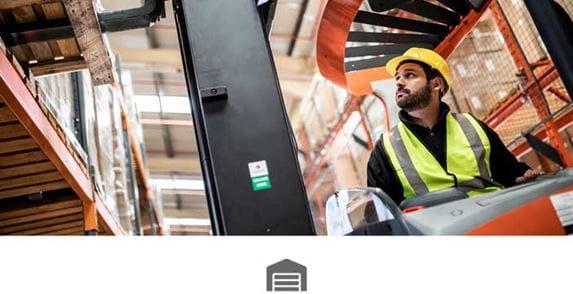 Male warehouse operativewearing yellow hard hat and hi-vis in forklift moving pallet