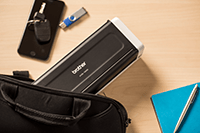 Portable compact document scanner ADS-1200 being put in a bag