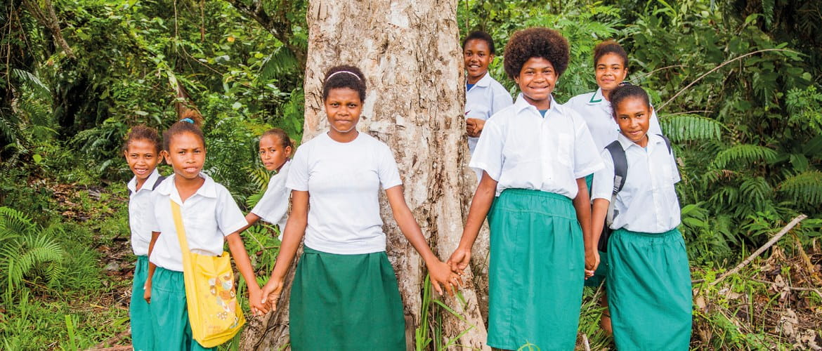 A group of eight students from a Brother and Cool Earth funded community scholarship pose next to a tree in a forest in Orangerie Bay, Papua New Guinea