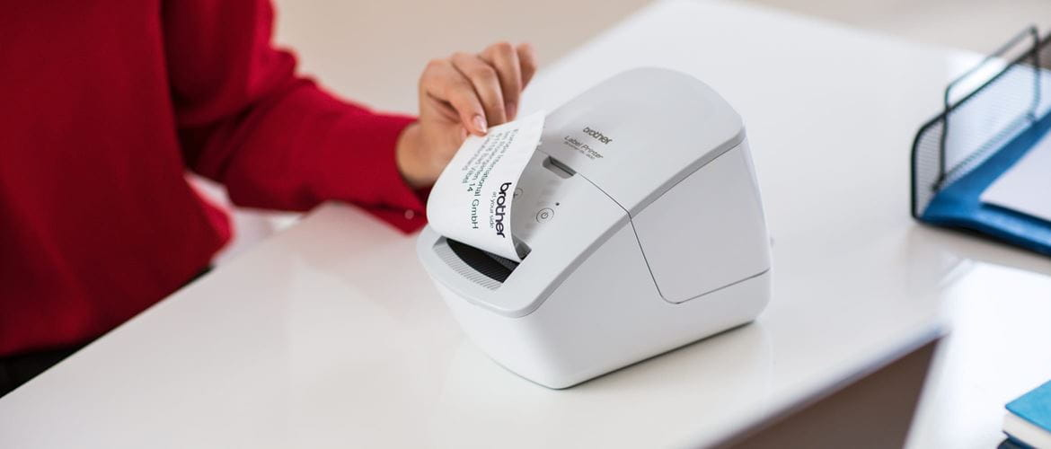 A lady wearing a red top removing a printed address label from a Brother thermal label printer which is on a desk in an office environment