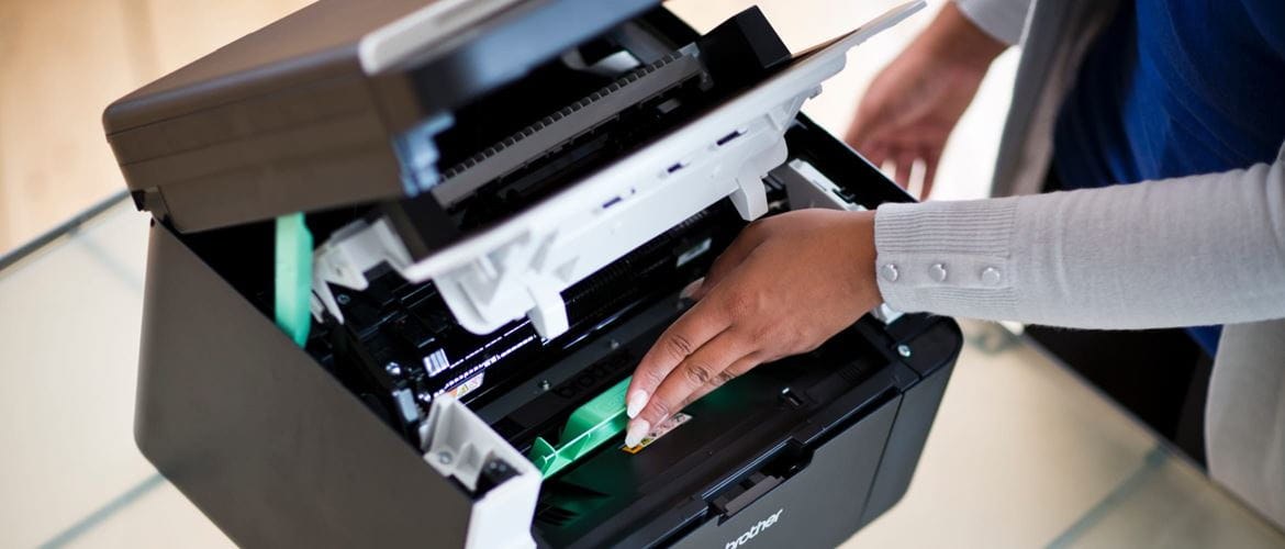 A lady inserting a toner cartridge into a laser printer, revealing the inner workings